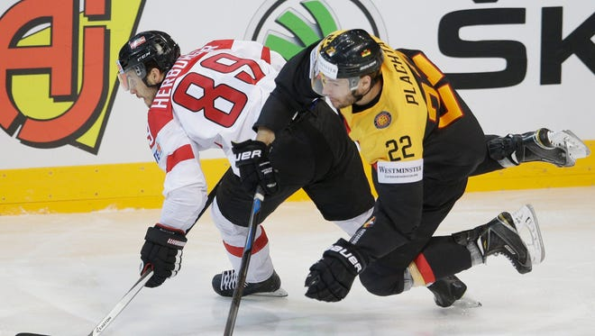 Germany's Matthias Plachta, right, collides with Austria's Raphael Herburger, left, during the Hockey World Championships Group A match in Prague, Czech Republic, Monday, May 11, 2015.