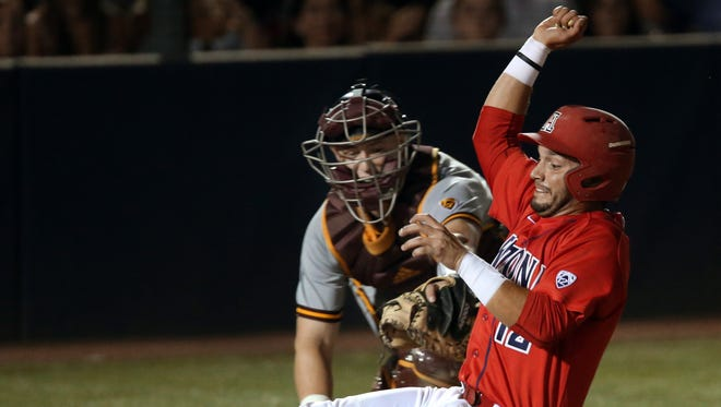 Arizona Cesar Salazar (12) slides home just ahead of the tag from Arizona State catcher Brian Serven (24) to open the night's scoring on Cody Ramer's (13) sacrifice fly in the fifth inning of their Pac-12 showdown at Hi Corbett Field, Saturday, May 14, 2016, Tucson, Ariz.