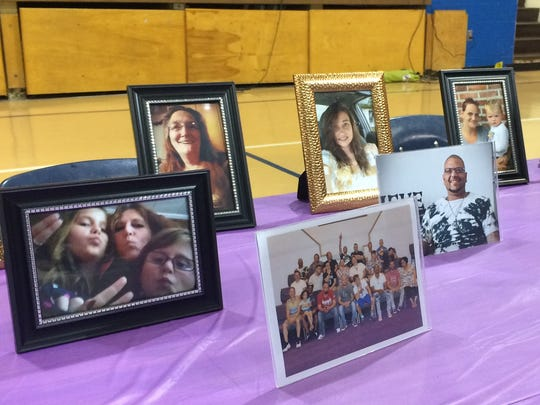 Pictures of local people in recovery sit on a table during the 2018 Steps of Change event at Mt. Logan Elementary. The annual event focuses on celebrating those in recovery and connecting those in need to recovery services.