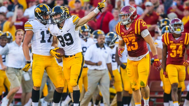 Iowa's Matt VandeBerg (89) points downfield after a first-down reception in front of Iowa State's Darian Cotton, right, during the Hawkeyes' 31-17 win.
