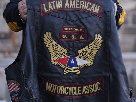"""Mike Montalvo, president of the Empire State chapter of the Latin American Motorcycle Association, holds his """"colors"""" on Wednesday."""