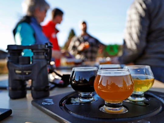 In this Sunday, Nov. 13, 2016 photo a group of birding enthusiasts finish discuss their day while sampling a flight of beers at the Maine Brewing Company in Freeport, Maine. The Maine Brew Bus tour group combines bird watching and craft beers into popular trips throughout southern Maine.