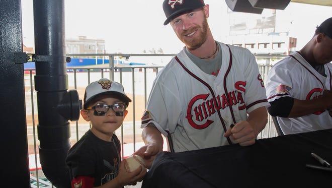 El Paso Chihuahua reliever Derek Eitel makes a young fan happy.
