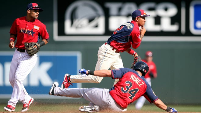 USA infielder J.P. Crawford (top) turns a double play over World infielder Renato Nunez in the 4th inning July 13 during the All Star Futures Game at Target Field. Credit: Jerry Lai-USA TODAY Sports