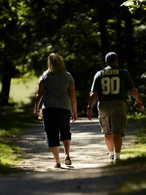 Paula Dramm and husband Seth Dramm, both of Manitowoc, enjoy a leisurely stroll through the trail at Rawley Point to get some healthy exercise while enjoying nature underneath a canopy of leaves on Aug. 31, 2013.