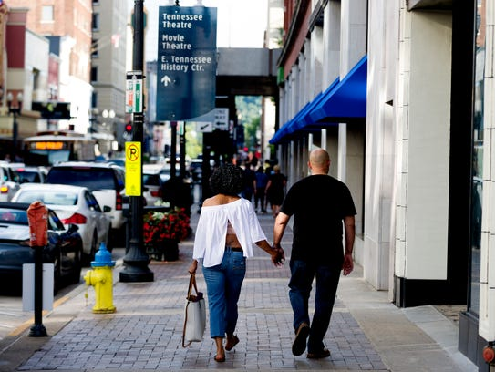 A couple walks down Gay Street in Knoxville, Tennessee