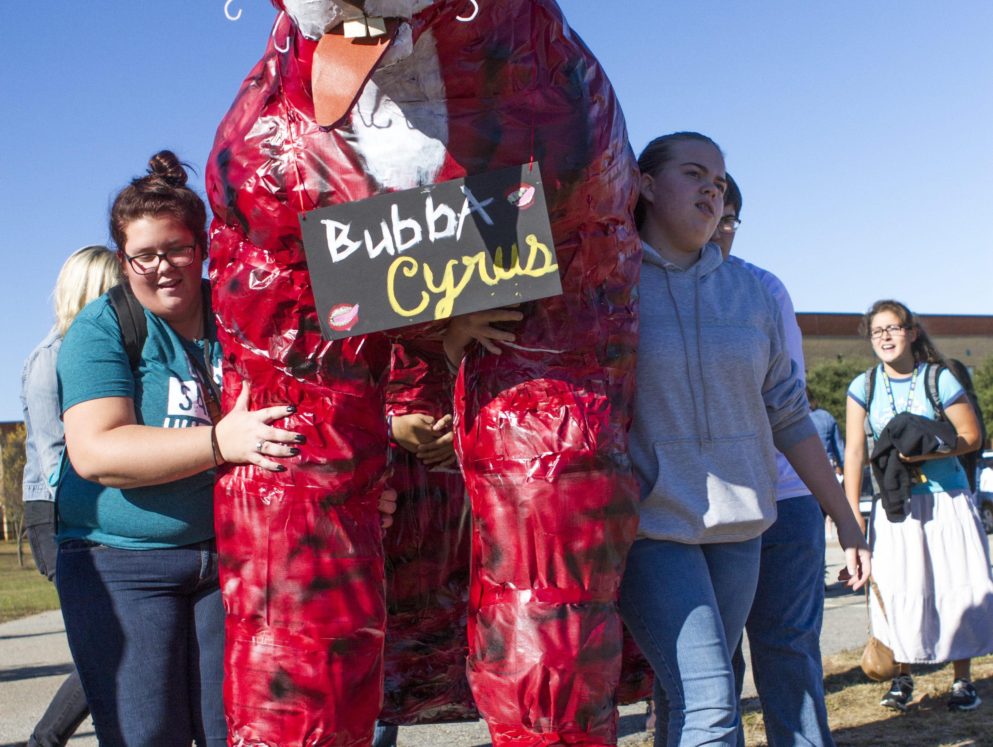 Greer High School art students pack Bubba Cyrus, their Tiger project, toward his final resting place. Cyrus will be burned following the school's pep rally leading to their rivalry game against Blue Ridge High School.