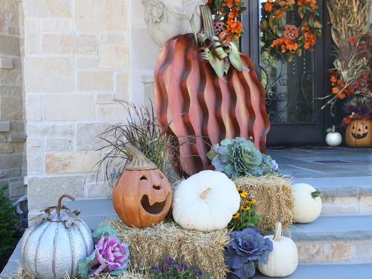 Large metal pumpkins and bales of hay decorate a front porch.