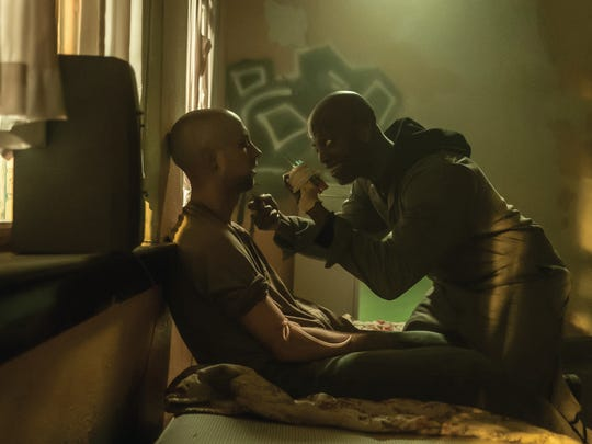 """Skeletor (Rotimi Paul) kneels over an addict in """"The First Purge."""""""