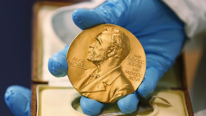 In this April 17, 2015, file photo, a national library employee shows a gold Nobel Prize medal in Bogota, Colombia.