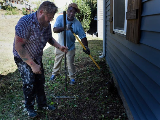 Peter Matteson and Daryl Samuels clean up old landscaping