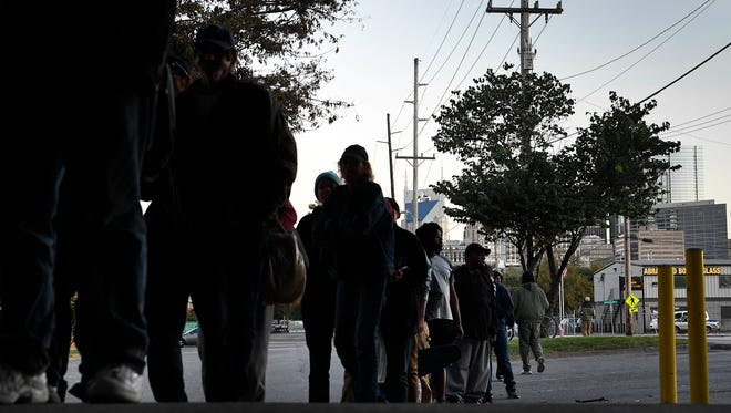 Homeless men and women line up to receive a meal under the Kelly Miller Smith memorial bridge Wednesday, Oct. 18, 2017, in Nashville.