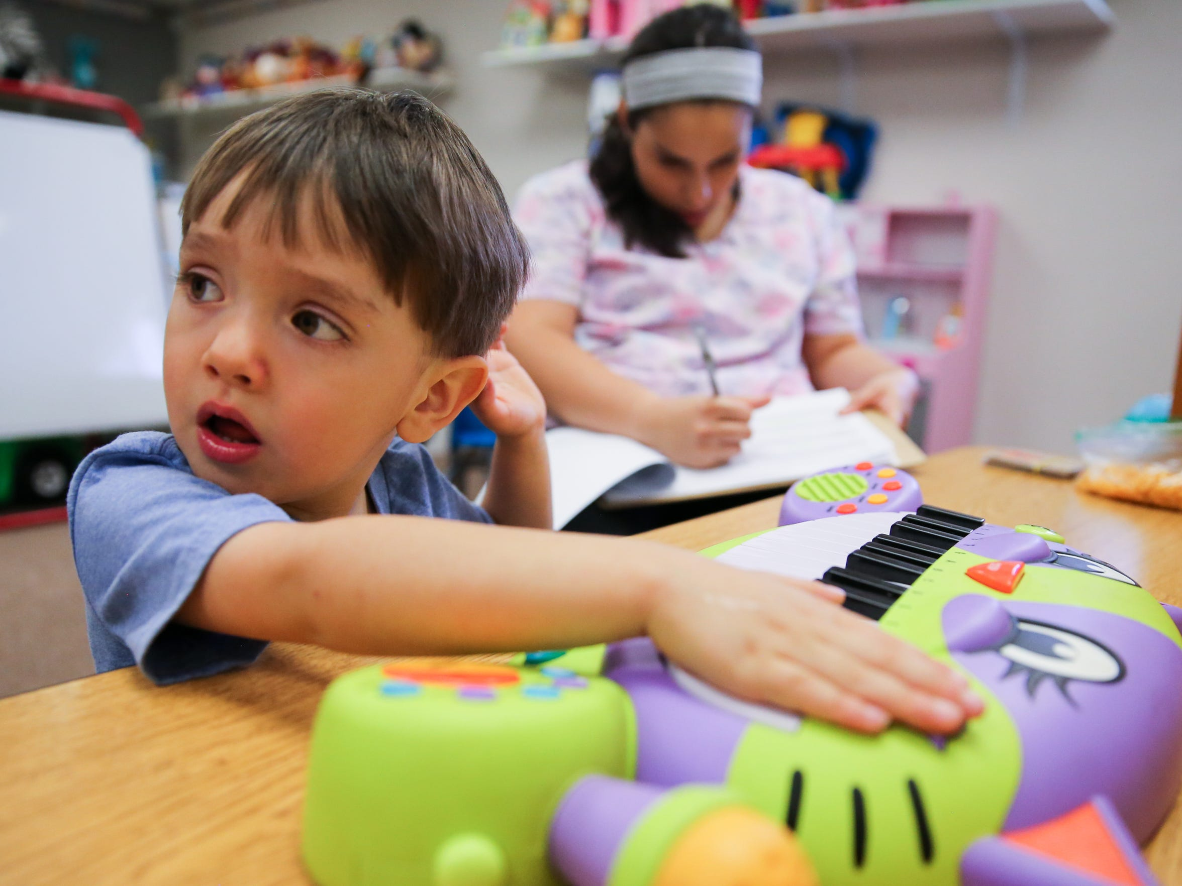 Mykaela Lara, registered behavior technician, makes notes while Aiden Lopez, 3, plays during ABA Therapy at ABC Autism Center for Children through MHMR Services for the Concho Valley.