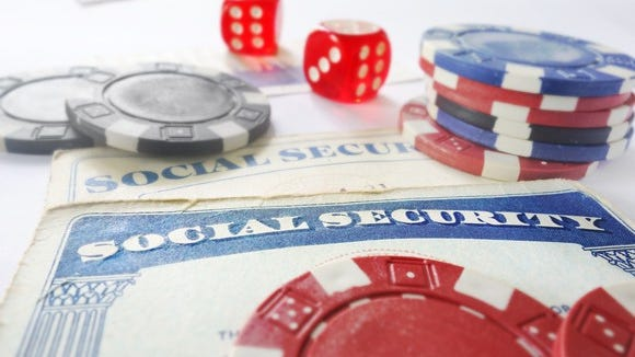 Casino chips and dice lying atop Social Security cards.