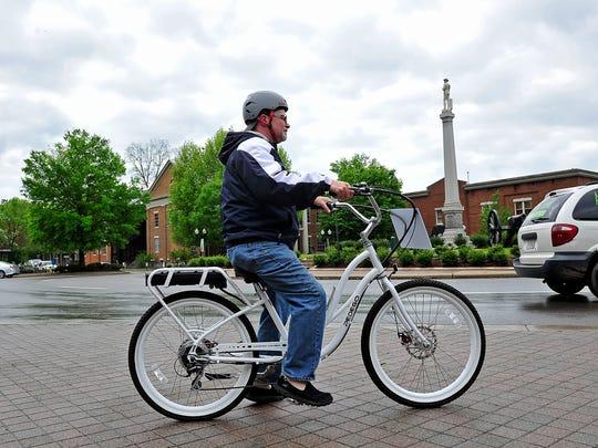 Historian and tour guide Kraig McNutt rides an electric