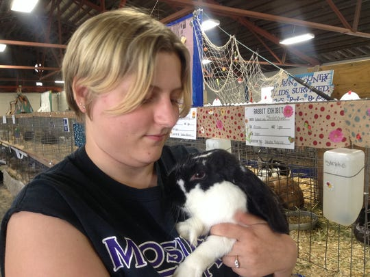 Kelsey Koprowski, 19, of Mosinee, admires one of her two rabbits, Diesel, at the Wisconsin Valley Fair Wednesday.