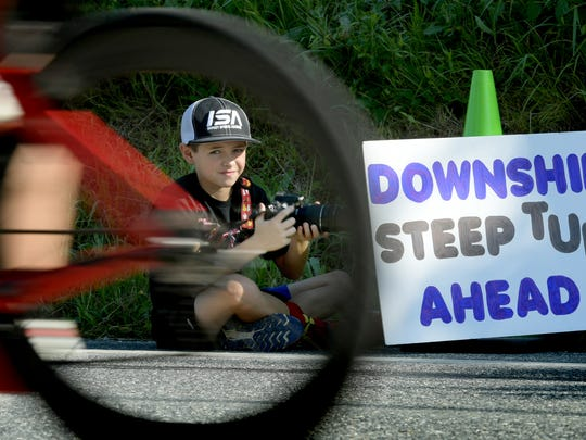 Everett Sachs, 9, of Green Bay, Wisconsin, photographs riders during the 14th Annual YWCA York Y-Tri at Lake Redman Sunday, June 24, 2018. Everett, whose family was visiting in Baltimore, was waiting to get a photo of his older brothers competing in the race. Competitors completed a 500-yard swim, 15-mile bike ride and 5K run during the event. Bill Kalina photo