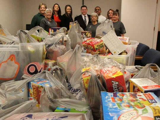 Western Commerce Bank employees and Packs for Hunger volunteers posed with the donations collected by the bank.