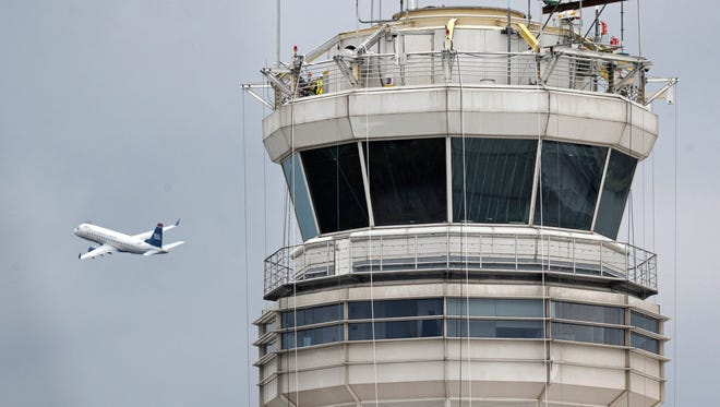 A passenger jet flies past the FAA control tower at Washington's Ronald Reagan National Airport. Air traffic control systems are one possible target of cyber terrorists, experts say.