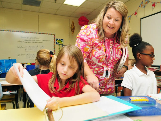 Third grader Lurah Anderson, 8, prepares her binder as language arts teacher Jennifer Delatte looks on during the first day of school at Petal Elementary.