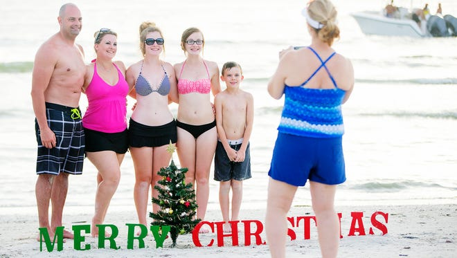 """The Aurand family, Kenny, left, his wife Katrina and children Tiffany, 12, Trinity, 14, and Skyler, 10, enjoy Christmas on Fort Myers Beach on Friday. """"It doesn't feel like Christmas. But, we don't mind the weather,"""" said Katrina. The family is on vacation from Ohio."""