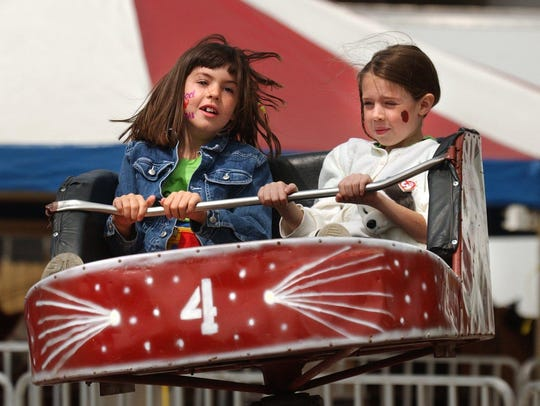 Lauren Clark, 7, and her sister Sara, 8, ride one of