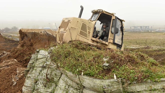 Louisiana National Guard Pfc. Austin Burdette, of Walker, assigned to the 769th Brigade Engineer Battalion, 256th Infantry Brigade Combat Team, repairs a levee in Krotz Springs in advance of expected river flooding, Jan. 8, 2016.