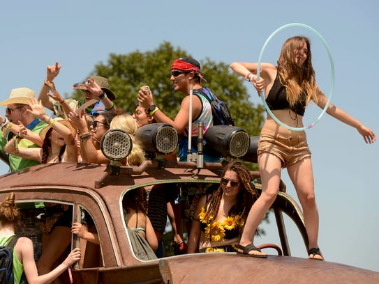 Guests dance on top of Big Red, an oversized art car,