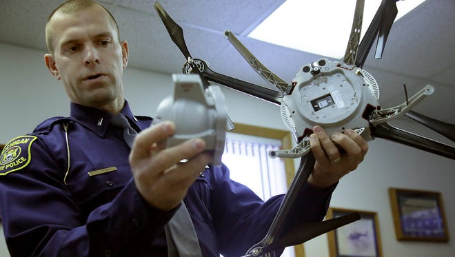 First Lt. Chris Bush, Michigan State Police Commander  of Field Support and Aviation Section, holds an unmanned aerial vehicle that the police force has been training with since 2013 regulated by the Federal Aviation Administration at the Michigan State Police headquarters in Lansing, Mich. on Friday, Nov. 21, 2014. The UAV has a infared camera attached for viewing.