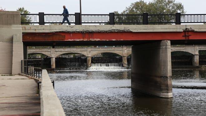 A man crosses a bridge over the Flint River near the Hamilton Dam in downtown Flint on Thursday, Oct. 8, 2015,