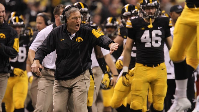 Iowa head coach Kirk Ferentz high-five's players after a fumble recovery during the Hawkeyes' Big Ten Championship game against Michigan State at Lucas Oil Stadium in Indianapolis, Ind. on Saturday, Dec. 5, 2015.