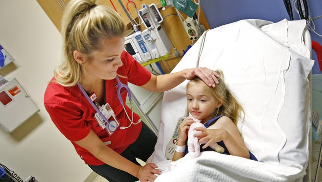Registered nurse Lauren Madden checked on patient Nevaeh DeVault, 5, in the Riley Hospital ER this month. Madden is a former Colts cheerleader who who used to help entertain children at the annual Colts Christmas caroling at Indiana University Health Riley Hospital for Children.