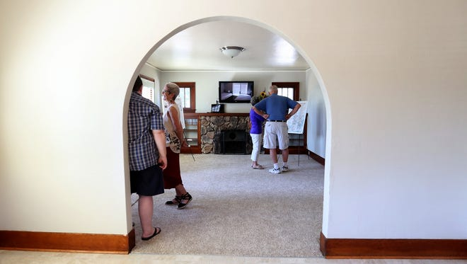 People gather in the living room during an open house at the Center for Hope and Safety's former safe house on Winter and Norway Streets NE in Salem on Thursday, July 13, 2017. The domestic violence shelter has opened a new safe home in an undisclosed location, and this event was to show where they had been safely housing victims for the past 39 years.