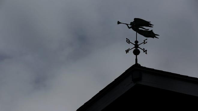 Dark clouds linger over a weather vane atop a Salem home on Sunday, Aug. 13, 2017.