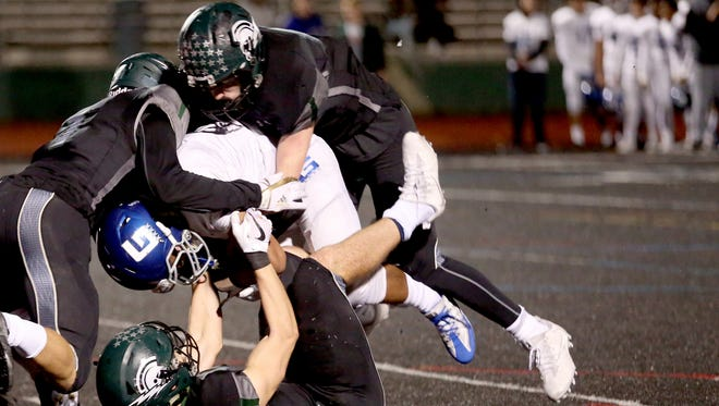 Grant's Demarques Singelton Jr. (7) is taken down by West Salem's Simon Thompson (1), Micah Pugh (17) and Alex Hurlburt (53) in the Grant vs. West Salem football game in the second round of the OSAA Class 6A playoffs at West Salem High School on Friday, Nov. 10, 2017.