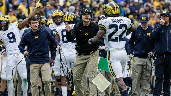 Jim Harbaugh high fives running back Karan Higdon in the second half of the Outback Bowl loss to South Carolina on Jan. 1.