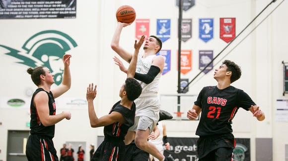West Salem's Kyle Greeley (5) goes up for a basket in a first-round playoff game against Clackamas on Wednesday, Feb. 28, 2018, at West Salem High School. The Titans won the game 88 to 69.