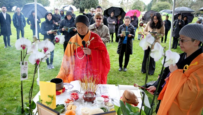 LiZhong Shifu, left, and Zhen Yuan Shifu lead a blessing during the Qing Ming Festival at Salem Pioneer Cemetery on Thursday, April 5, 2018. The traditional Chinese festival honors ancestors and celebrates the return of spring.