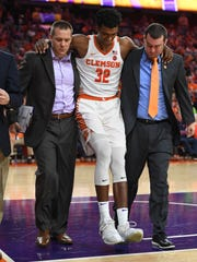 Clemson forward Donte Grantham (32) is helped off the court after injuring his right knee during the 2nd half against Notre Dame on Saturday, January 20,  2018 at Clemson's Littlejohn Coliseum.