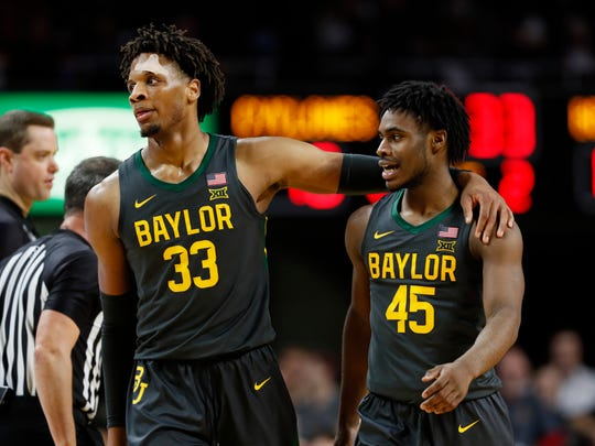 Baylor forward Freddie Gillespie (33) walks to the bench with Davion Mitchell (45) during the second half of the team's NCAA college basketball game against Iowa State, Wednesday, Jan. 29, 2020, in Ames, Iowa. Baylor won 67-53. (AP Photo/Charlie Neibergall)
