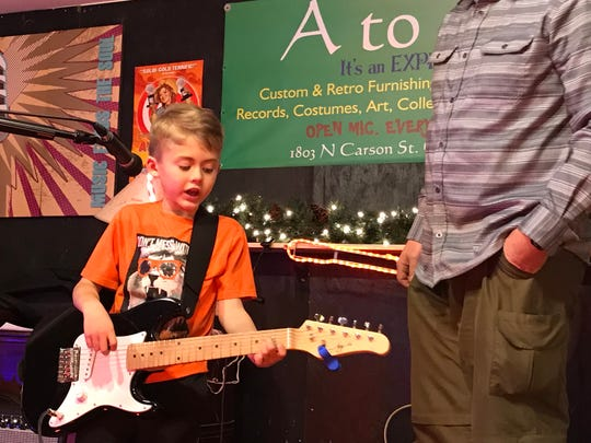 4. Six-year-old Clark Hoffman debuts his guitar techniques, playing four chords, with his father giving a tad of coaching, at the A to Zen open mic in Carson City.