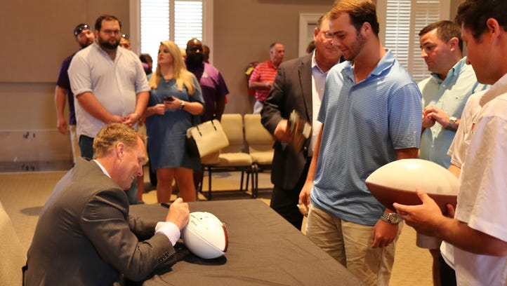 Ole Miss head football coach Hugh Freeze signs an autograph for a fan before speaking at Englewood Baptist Church on Saturday.
