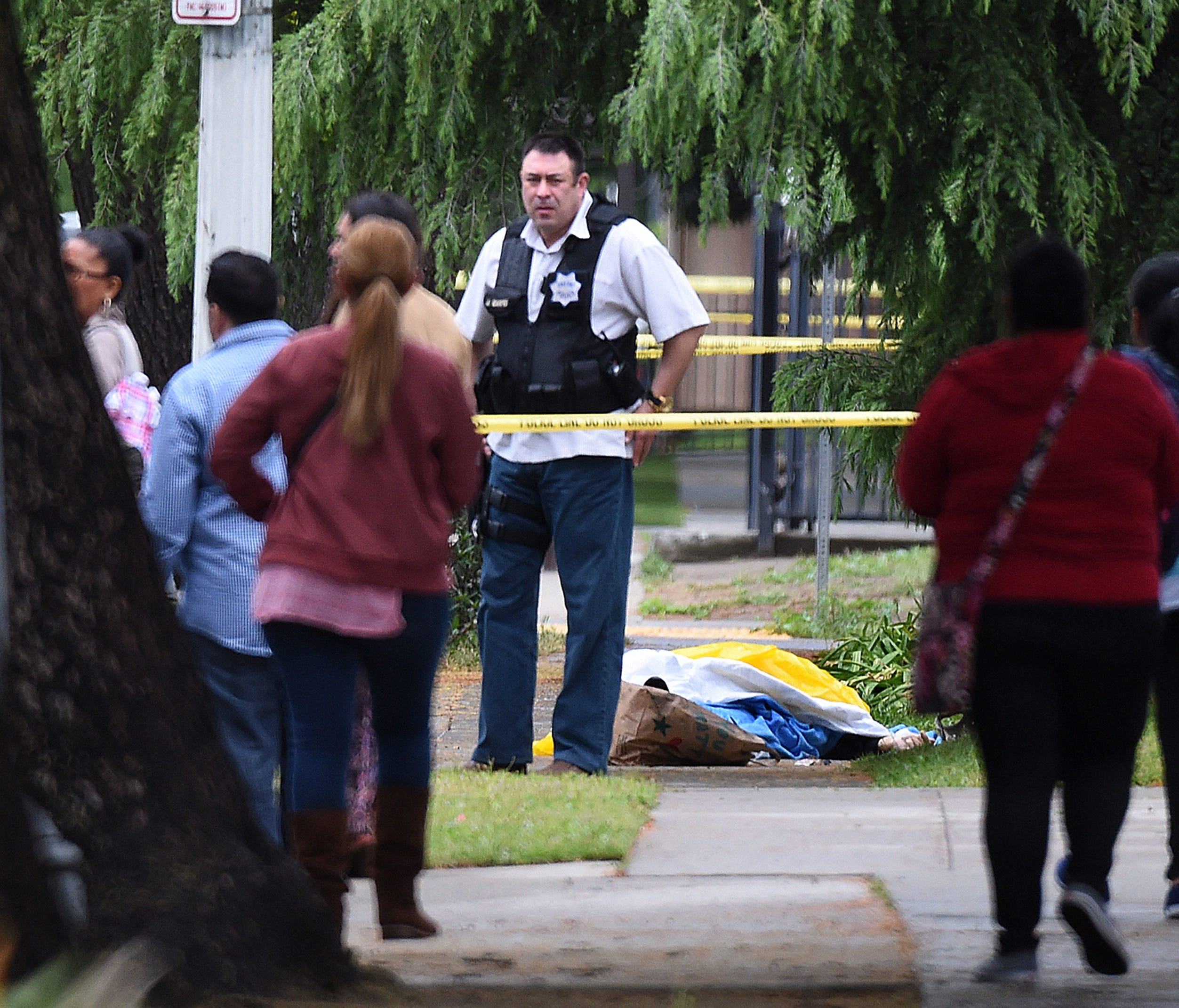 A Fresno police detective stands over the body of one of the three shooting victims Tuesday, April 18, 2017 in Fresno, Calif. A man shot and killed three people on the streets of downtown Fresno on Tuesday, shouting