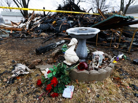Flowers sit in front of what remains of a house that caught fire on New Year's Day, killing two men.