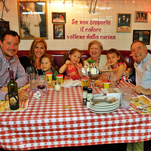 """It wasn't your typical Mother's Day brunch, but the Greazel family clearly enjoyed their """"behind the scenes"""" table in an Italian restaurant's kitchen in Chicago. From left are Ben Greazel, his wife, Ronnie, their daughters, Bella and Sofia, his mother, Janet, a third daughter, Olivia, and his father, Bill Greazel. Bill translates the wall message, """"If you can't take the heat, get out of the kitchen."""""""