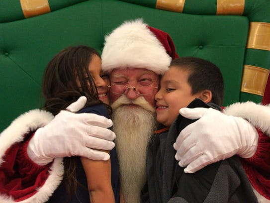Santa gives Mia Barrientez, 7, and brother Amadeo Barrientez IV, 6, a big hug after hearing what the two wanted for Christmas this year.