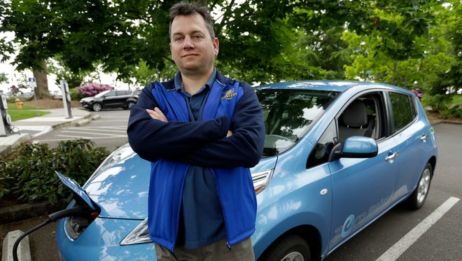 Patrick Conner, who has been driving an electric car since 2007, poses with his Nissan Leaf at a charging station at the public library in Hillsboro, Ore., Tuesday, May 19, 2015.    Fuel-efficient, hybrid and electric cars are a boon for the environment, but their growing popularity means shrinking fuel tax revenues for state coffers and less money to pay for road and bridge projects. Oregon is about to embark on a first-in-the-nation program that aims to address this shortfall by testing the feasibility of taxing motorists not for the fuel they use, but for the miles they drive. (AP Photo/Don Ryan)
