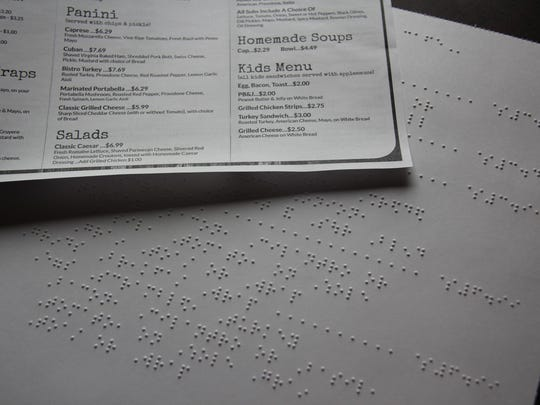A menu in Braille, juxtaposed with a non-Braille menu, at Grinds 122 Café in Brockport.