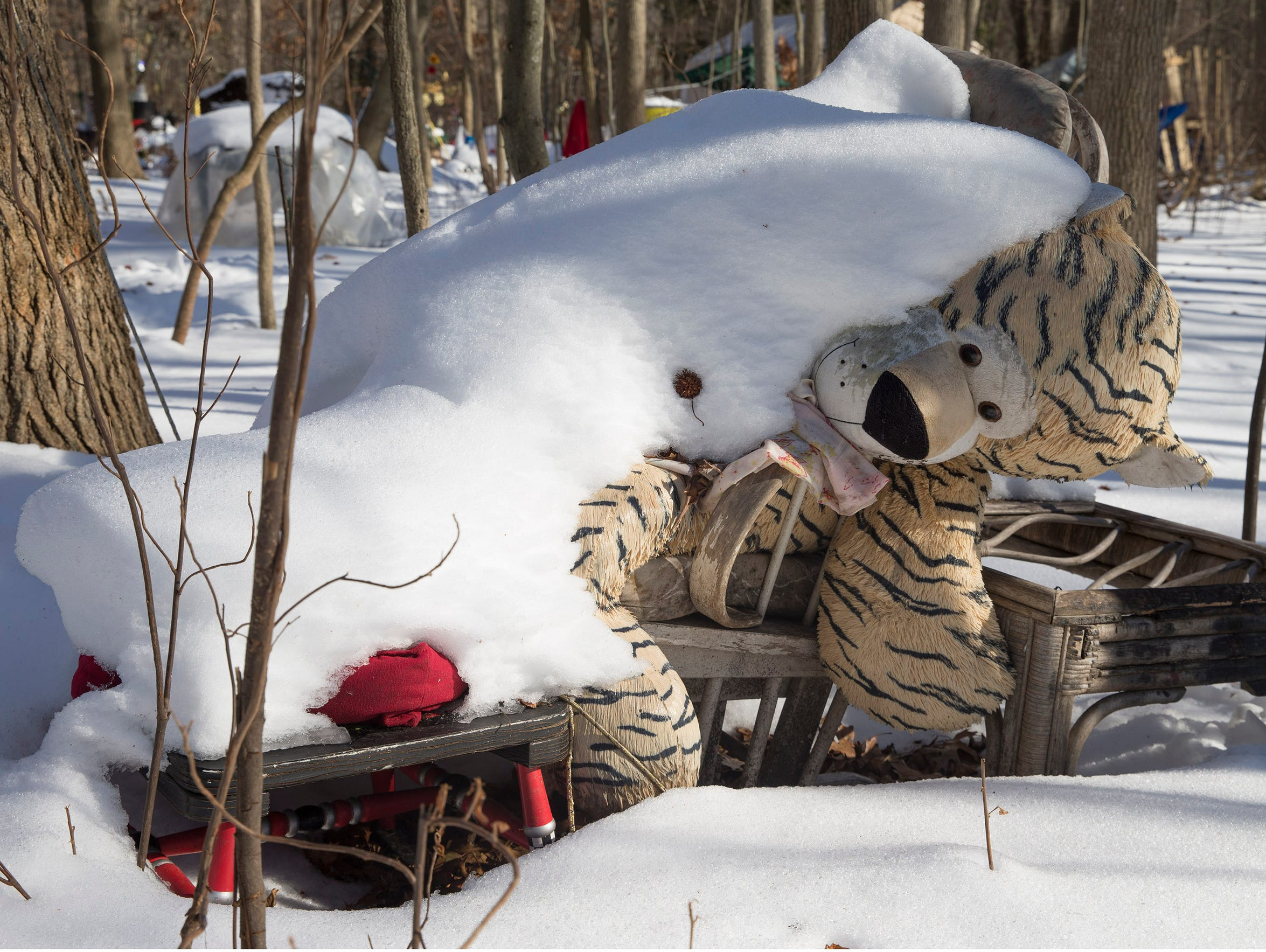 Snow covers a large stuffed tiger used as a sort of lawn ornament to mark the property of a resident in the Neptune homeless encampment