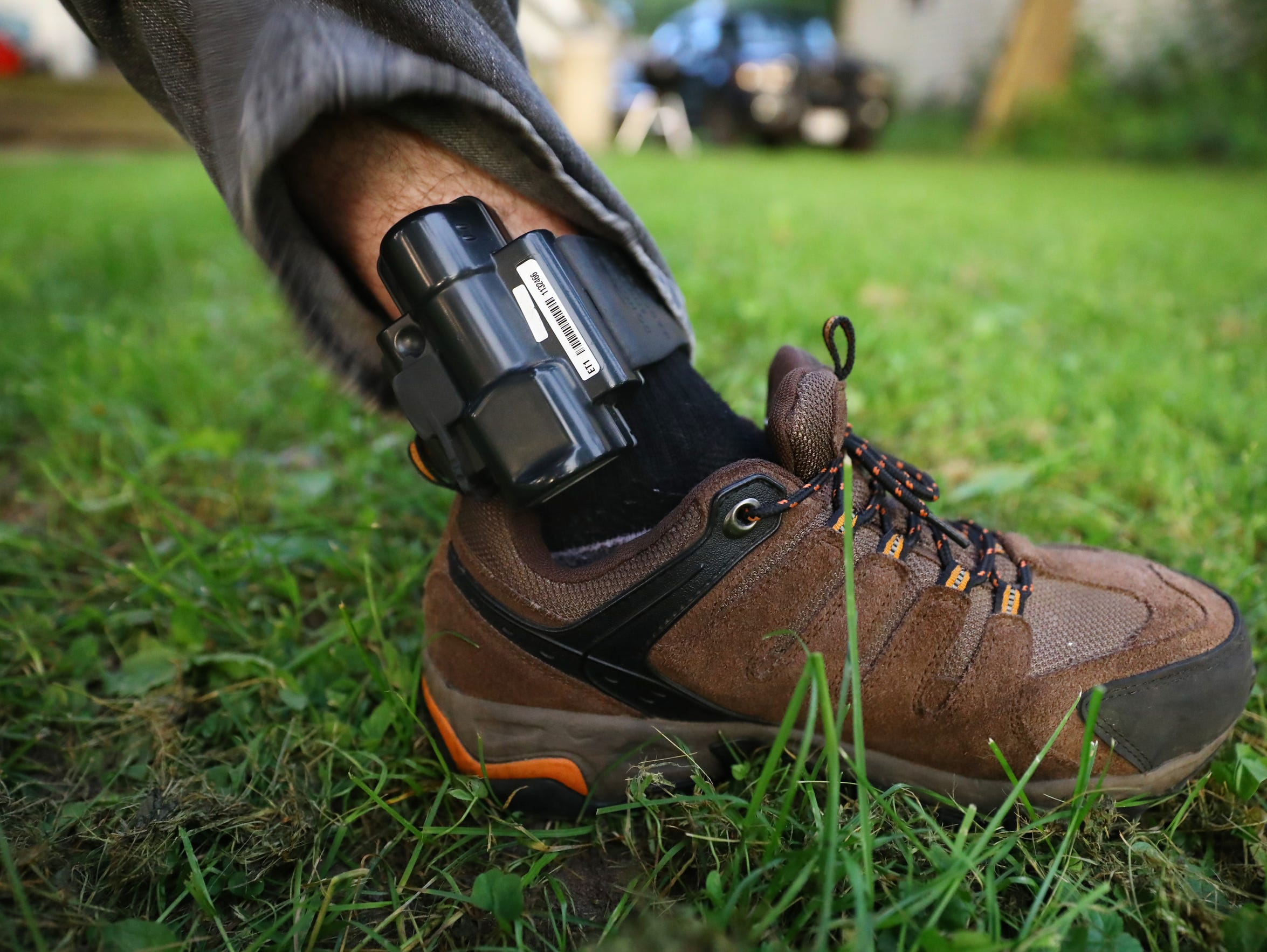 Cody McCormick, 29, shows the GPS monitoring device